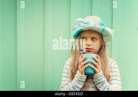 Cute little girl stands near a wall in turquoise hat and holding cup. - Stock Photo