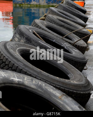 black tires leaning against wharf's edge with ocean in background. - Stock Photo