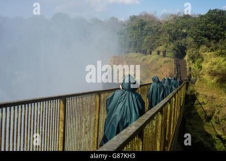 Visitors walk across the bridge near Victoria Falls, Livingstone, Zambia - Stock Photo