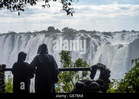 Visitors looking at Victoria Falls in Livingstone, Zambia - Stock Photo