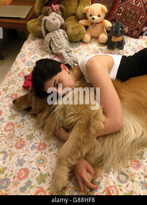 woman sleeping on bed with golden retriever dog - Stock Photo