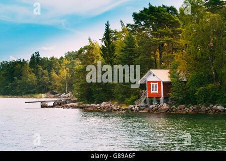 Red Small Finnish Wooden Sauna Log Cabin On Island In Autumn Season. - Stock Photo