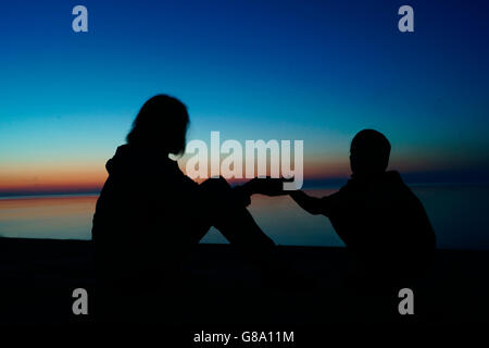 Jurmala, LV. 23rd June, 2016. Mother and her son in silhouette sitting on a sandy seashore watching the sunset at - Stock Photo