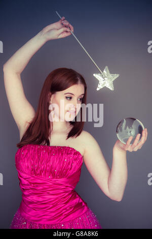 Fortune teller: A young woman girl  holding a large crystal glass ball in one hand and a magic star wand in the - Stock Photo