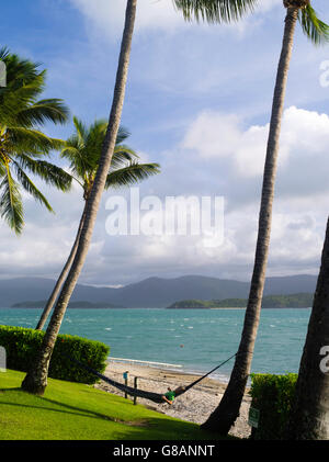 A boy relaxes in a hammock next to the beach on Daydream Island; Whitsunday Islands, QLD, Australia - Stock Photo