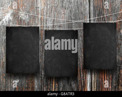 Close-up of three blank blackboard frames hanged by pegs against dark wooden boards background - Stock Photo