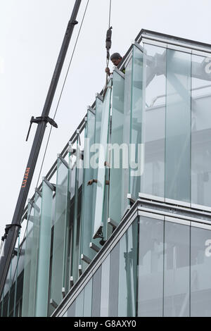 Workmen fitting external glass louvres on energy efficient new office block in Spain - Stock Photo