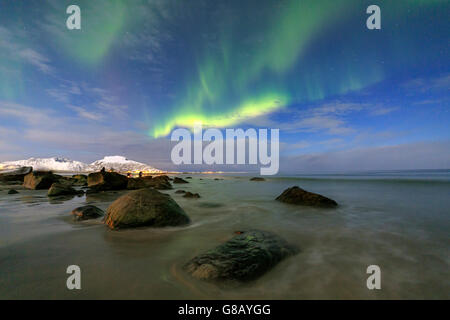 Northern Lights illuminate the landscape around Gymsøyand and the snowy peaks Lofoten Islands Northern Norway Europe - Stock Photo