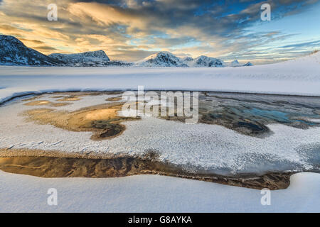 The golden sunrise reflected in a pool of the clear sea where the snow has melted Haukland Lofoten Islands Norway Europe
