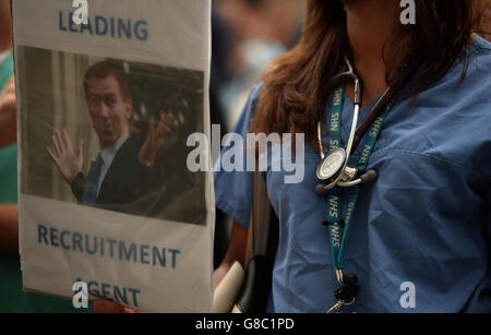 A woman holds a placard during the 'Let's Save the NHS' rally and protest march by junior doctors in London. - Stock Photo