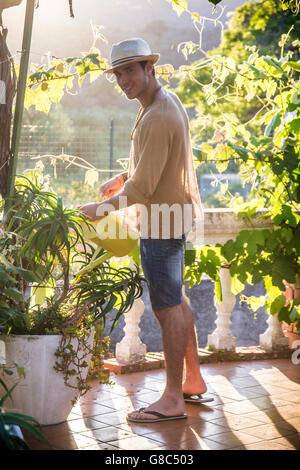 Side view of young stylish man watering plants in garden in sunlight - Stock Photo