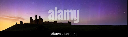 The Northern Lights dance gently behind the ruins of Dunstanburgh Castle, Northumberland, UK - Stock Photo