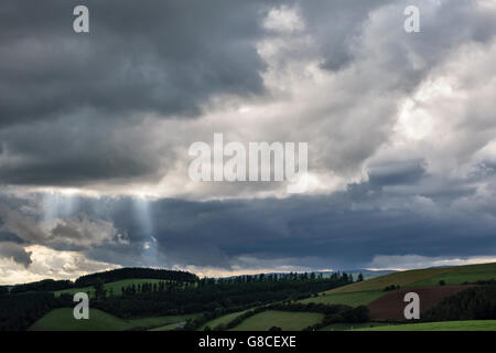 Near Knighton, Powys, UK, on the border between England and Wales. Beams of sunlight breaking through dark stormclouds - Stock Photo