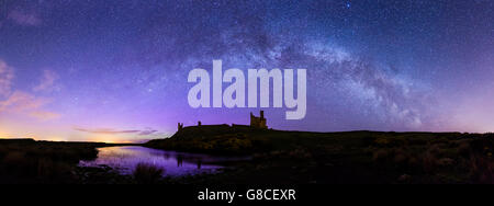 Dunstanburgh Castle with the Milky Way and Northern Lights - Stock Photo