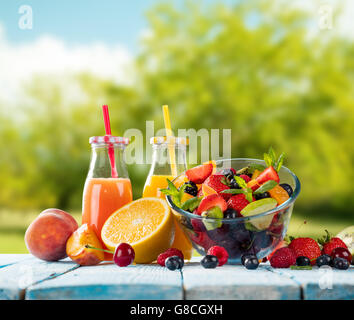 Fresh glasses of juice and salad with fruit mix placed on wooden planks. blur garden on background. Concept of healthy - Stock Photo