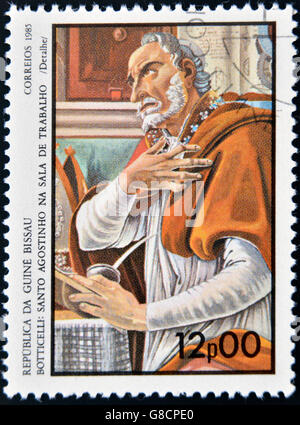 GUINEA BISSAU - CIRCA 1985: a stamp printed in Guinea-Bissau shows St. Augustine in the work room by Botticelli, - Stock Photo