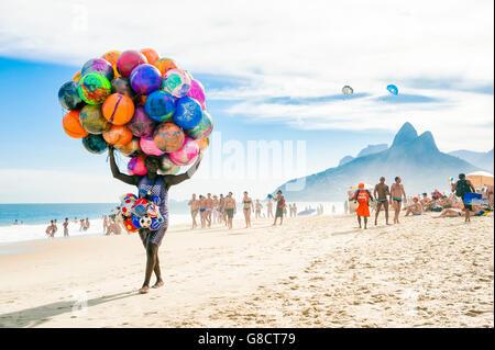 RIO DE JANEIRO - JANUARY 20, 2013: Beach vendor selling colorful beach balls carries his merchandise along Ipanema - Stock Photo