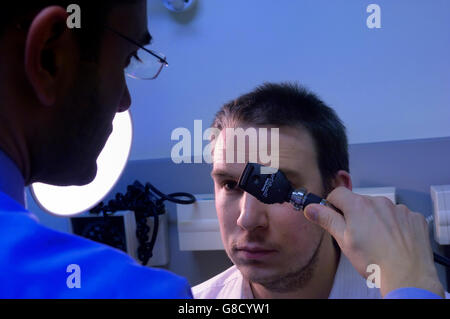 Eye examination using a Ophthalmoscope - Stock Photo