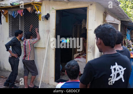 men crowd around a house to watch the television inside showing india versus pakistan in the world cup cricket, - Stock Photo
