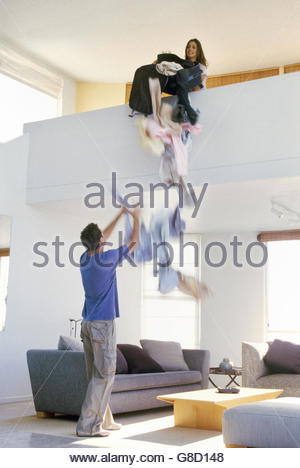 View of woman dumping clothes from a balcony onto boyfriend - Stock Photo