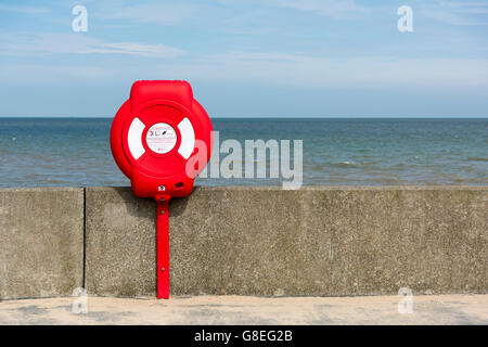 A lifebouy on the sea wall at Walton on the Naze by the north sea coast in the UK - Stock Photo