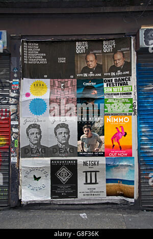 Various posters on a wall in Redchurch Street, Shoreditch, East London, UK. - Stock Photo