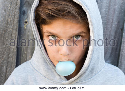 Portrait of aggressive teenage boy with hoodie blowing bubble gum against grey wooden fence