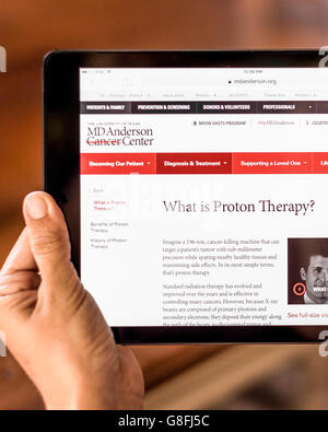 A Caucasian young woman's hands are seen holding an iPad while researching Proton Therapy. - Stock Photo