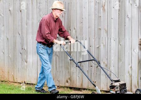 A senior Caucasian man mows his lawn in Oklahoma City, Oklahoma, USA. - Stock Photo