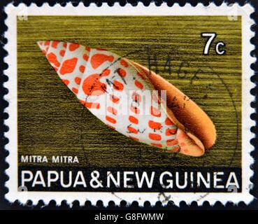 PAPUA NEW GUINEA - CIRCA 1969:  A stamp printed in Papua New Guinea shows shell Mitra mitra (Episcopal miter), circa - Stock Photo