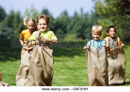Boys and girls in a sack race - Stock Photo