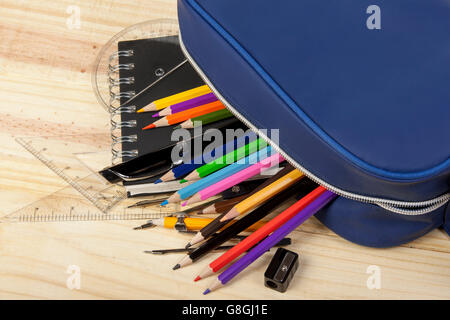 Blue school pencil case spilling it's contents  out onto wooden classroom desk showing colouring pencils pencil - Stock Photo