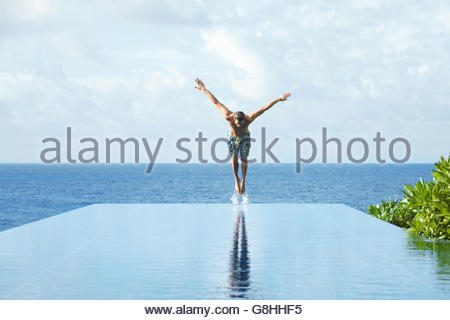 Young man diving in pool - Stock Photo