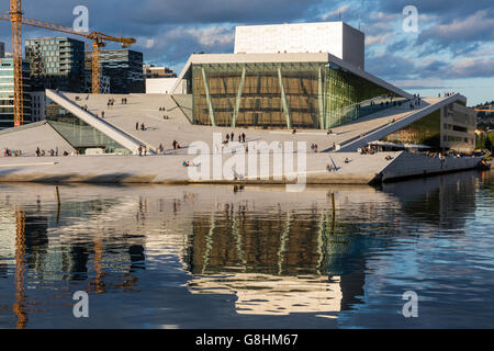 Oslo Opera House reflected in the bay at sunset - Stock Photo