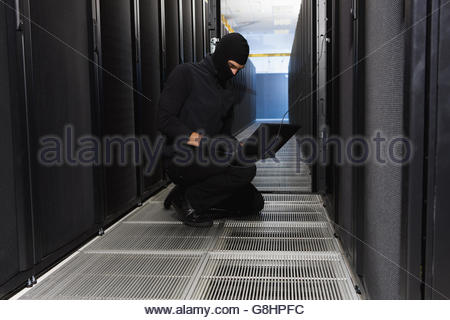 Man in ski mask hacking into server room in Cape Town, South Africa - Stock Photo