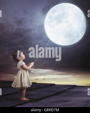 Fairy portrait of a little cute girl with a moony balloon - Stock Photo