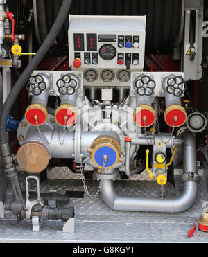 big automatic pump nozzles in fire truck with gauges and controls - Stock Photo