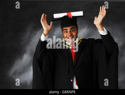 Studio shot of a male student graduate in gown with scroll on hat expressing enormous joy for achieving his university - Stock Photo