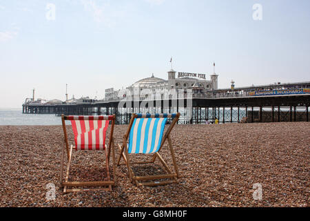 Deckchairs looking out at Brighton Pier - Stock Photo