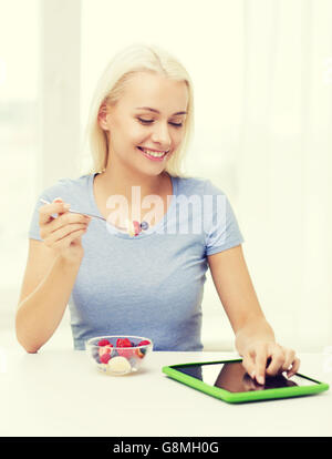 smiling woman eating fruits with tablet pc at home