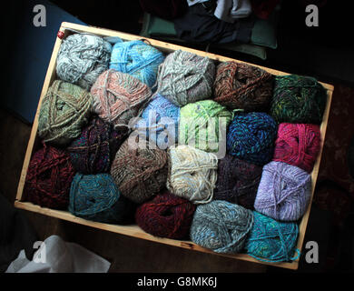 A display box of hand knitting yarns in various shades from blues, browns through to reds and greens. - Stock Photo