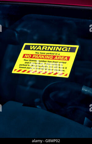 WARNING! sticker on windshield of vehicle parked illegally.  Vertical shot. - Stock Photo