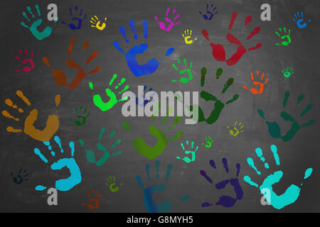 Many colorful painted hands printed on a blackboard - Stock Photo