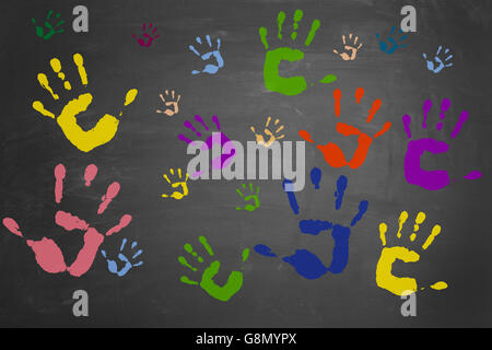 Many different colorful hand prints on a blackboard - Stock Photo