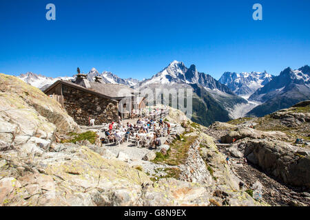 Hikers admire the Mont Blanc massif from Refuge of Lac de Cheserys Haute Savoie France Europe - Stock Photo