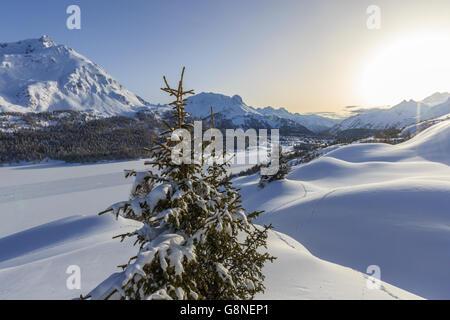 Sun shines on the snow capped mountains Maloja Pass Engadine Switzerland Europe - Stock Photo