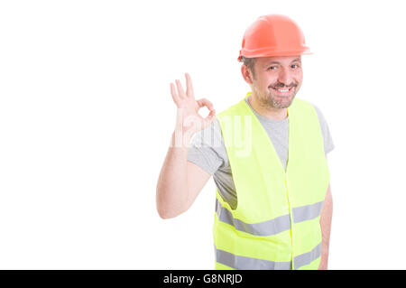 Joyful young builder wearing vest and helmet showing ok sign as good work concept isolated on white with copyspace - Stock Photo