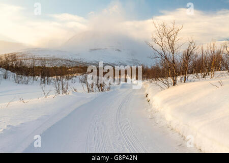 Winter landscape in Nikkaluokta with a winter road going towards big mountains in the background taken at sunset, - Stock Photo
