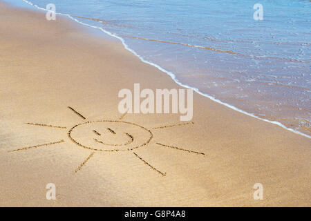 Smiley face sun drawing on a beach. UK - Stock Photo