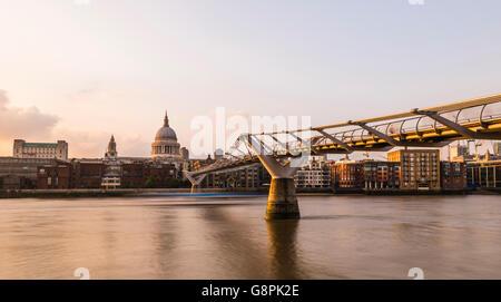 Glorious orange light of dusk on the Millennium Bridge at Bankside, London, UK. - Stock Photo